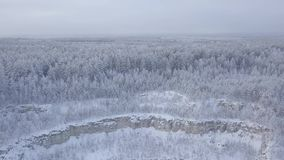 View snow-capped quarry and forest from a bird`s-eye view. The beginning of winter days stock video