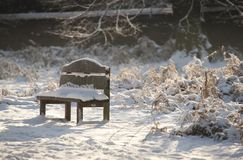 A view of a snow covered empty bench in the grounds of the Elizabethan Wollaton Hall museum and gardens in the snow in winter in stock images