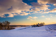 View of snow covered farm fields and rolling hills at sunset in Stock Photo