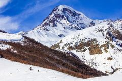 View of the snow-covered Kazbek, a group of skiers rises to the top. Winter landscape, top view. View of the snow-covered Kazbek, a group of skiers rises to the Royalty Free Stock Image