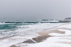 View of snow-covered pier and the sea during a snowfall in winte Royalty Free Stock Images