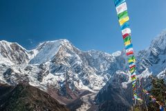 View of snow covered range of Mount Manaslu and prayer flags 8 156 meters with clouds in Himalayas, sunny day at Manaslu Glacier. In Gorkha District in northern stock photography