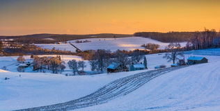 View of snow covered rolling hills and farm fields at sunset in Stock Photography