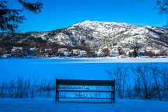 Winter Landscape with A Snowy Bench by A Frozen Lake, Snowy Mountain and Blue Color stock image