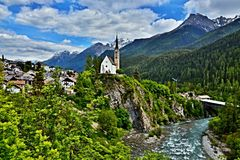 Swiss Alps-view of the river Inn and the church in town Scuol. View of the snowy peaks of the Alps and the river Inn and the church in town Scuol in Swiss Alps Royalty Free Stock Images