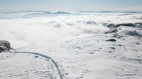 A view of the snowy slope on the valley covered with fog stock images