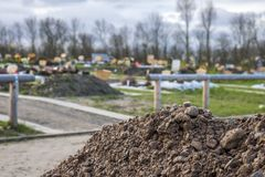 View of soil with blurred graves in the background Stock Image