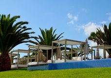 View of some beds sunloungers and palm trees on a green grass in a beach club of Tenerife,Canary Islands,Spain. Travel,vacation,relax concept royalty free stock photos