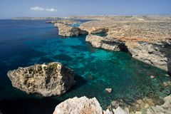 Turquoise Sea And Rocky Coastline, Malta. View from some cliffs on Comino, Malta. The island in the background is Gozo, in between lies the Blue Lagoon Royalty Free Stock Photos