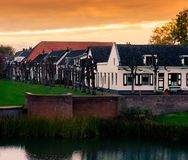 View on some modern houses with water and grass at sunset in the city Leerdam the Netherlands, typical dutch neighborhood royalty free stock image