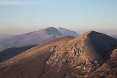 A view of some mountains top, beneath an empty blue sky at golden hour royalty free stock photo