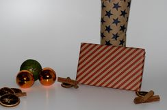 View on some orange and green christmas balls and christmas decoration and with two presents and with a white background and under. Ground in the district stock photos