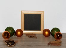 View on some orange and green christmas balls and christmas decoration on a wooden ground and with a white background in the distr. Ict emsland in germany royalty free stock image