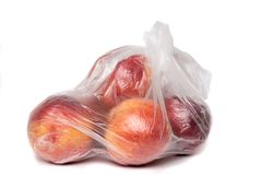View of some peaches inside a plastic bag. View of some peaches inside a plastic bag  on a white background Stock Image