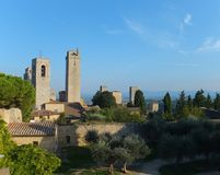 View of some of the towers of San Gimignano, Italy against blue sky, from the Parco della Rocca full of trees. View of some of the towers of San Gimignano, Italy stock image