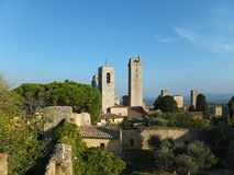 View of some of the towers of San Gimignano, Italy against blue sky, taken from the Parco della Rocca. Full of trees, with shadows cast by the low sun creeping stock image