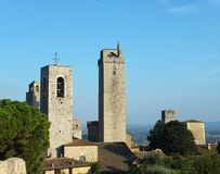 View of some of the towers of San Gimignano, Italy, standing tall against blue sky. Taken from the Parco della Rocca royalty free stock photos