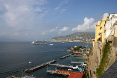 View of Sorrento, Italy's dock with a cruise ship off the coast. Summer day view of a cruise ship docked in the Bay of Naples at Sorrento, Italy along side Stock Images