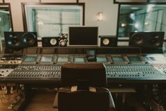 View of sound producing equipment at recording studio with armchair. On foreground royalty free stock images
