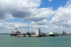 View of Southampton Docks with big cruise ship and cargo vessel on calm summer day with fine weather blue sky and white clouds Royalty Free Stock Images