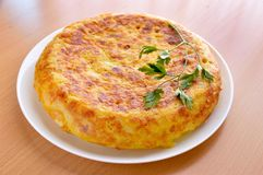 I love the spanish omelette. View of a spanish omelette with eggs potatoes and onion with parsley leaf on the top over a wooden table stock photos