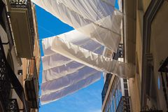 Shadow curtains on the street in Seville, Spain protecting tourists from sun and heat. View on Spanish street fits roof-like curtains. Way of cooling down the royalty free stock image