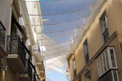 Shadow curtains on the street in Seville, Spain protecting tourists from sun and heat. View on Spanish street fits roof-like curtains. Way of cooling down the royalty free stock photo
