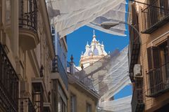 Shadow curtains on the street in Seville, Spain protecting tourists from sun and heat. View on Spanish street fits roof-like curtains. Way of cooling down the stock photo