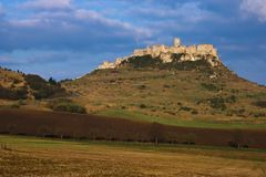 View of the Spis castle with the field underneath from the east at sunrise in early spring. A eastern view of the Spis castle taken from a nearby field at royalty free stock photos
