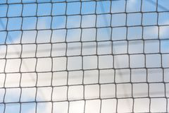 Sports net closeup view with blue sky and clouds background. View of sports netting with blurred clouds background. Blue sky and clouds view through wire net Stock Photography