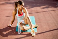 Sporty young woman relaxing and drinking water after training stock photos