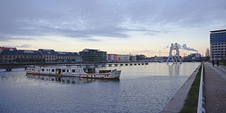 View on spree river with abandoned boat and Molecule Man statue in the background, berlin Royalty Free Stock Photography