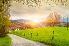 View of a spring day in the Switzerland, rural landscape at sunris. E - Switzerland rural sunset landscape. Countryside farm, green field, sun light and cloud Stock Images