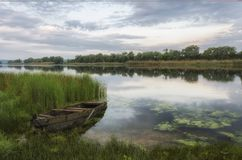 View of the spring river with a wooden boat near the shore stock photos
