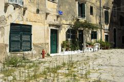 View of a square with grass growing everywhere in the old city in Corfu town in Greece, some white plastic chairs under a pergola. View of a square with grass royalty free stock images