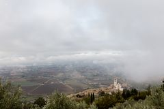 View of St. Francis papal church in Assisi Umbria, Italy in the middle of lifting morning fog. View of St. Francis papal church in Assisi Umbria, Italy, in the stock photos