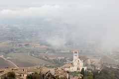 View of St. Francis papal church in Assisi Umbria, Italy in the middle of lifting morning fog. View of St. Francis papal church in Assisi Umbria, Italy, in the stock photo
