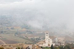 View of St. Francis papal church in Assisi Umbria, Italy in the middle of lifting morning fog. View of St. Francis papal church in Assisi Umbria, Italy, in the royalty free stock image