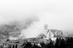 View of St. Francis papal church in Assisi Umbria, Italy in th. E middle of lifting morning fog royalty free stock photo