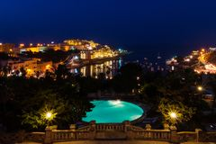 View of St. George`s Bay seafront lights by night, with a blue luxury swimming pool and boats and yachts anchored. Malta. royalty free stock image