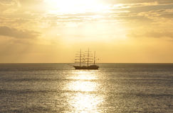 Masted sailing boat in golden path at sunset Royalty Free Stock Photos
