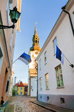 View of St.Mary Church and street with Estonian flags. Tallinn. Royalty Free Stock Photography