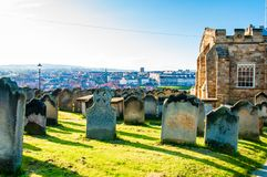 View of St Mary's Church, gravestones and Whitby Abbey in North Yorkshire, UK Stock Image
