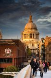 St paul`s cathedral with golden light. View of st paul`s cathderal during evening from millenium bridge with tourist royalty free stock photography