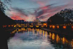 View of St Peter's Cathedral in Rome at sunset with lights reflecting upon the water of the Tiber River. Sunset view of St Peters Cathedral along the royalty free stock image
