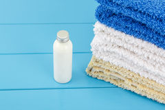 View of  stack of towels with little bottle of shampoo on a blue Royalty Free Stock Photo