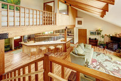 View from the staircase into the living room and kitchen room. Wooden beams on the ceiling. Royalty Free Stock Photos