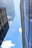 View standing between two tall glass skyscrapers looking straight up at both buildings reflecting each other and the sky - perspec. A View standing between two stock photos