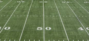 50 yard line on green football field. View from the stands of the green astroturf on an American football field showing 50 and 40 yard lines Stock Image