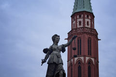 View of a statue of justice at Romerberg. Historical market square in Frankfurt. Alte Nikolaikirche gothic church dating to the middle ages in the background Stock Image